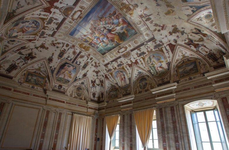 Vista grandangolare di una stanza di palazzo della Corgna. Sopra le luminose finestre sulla parete di destra, si erge un soffitto maestosamente affrescato con varie scene e numerosissime grottesche.