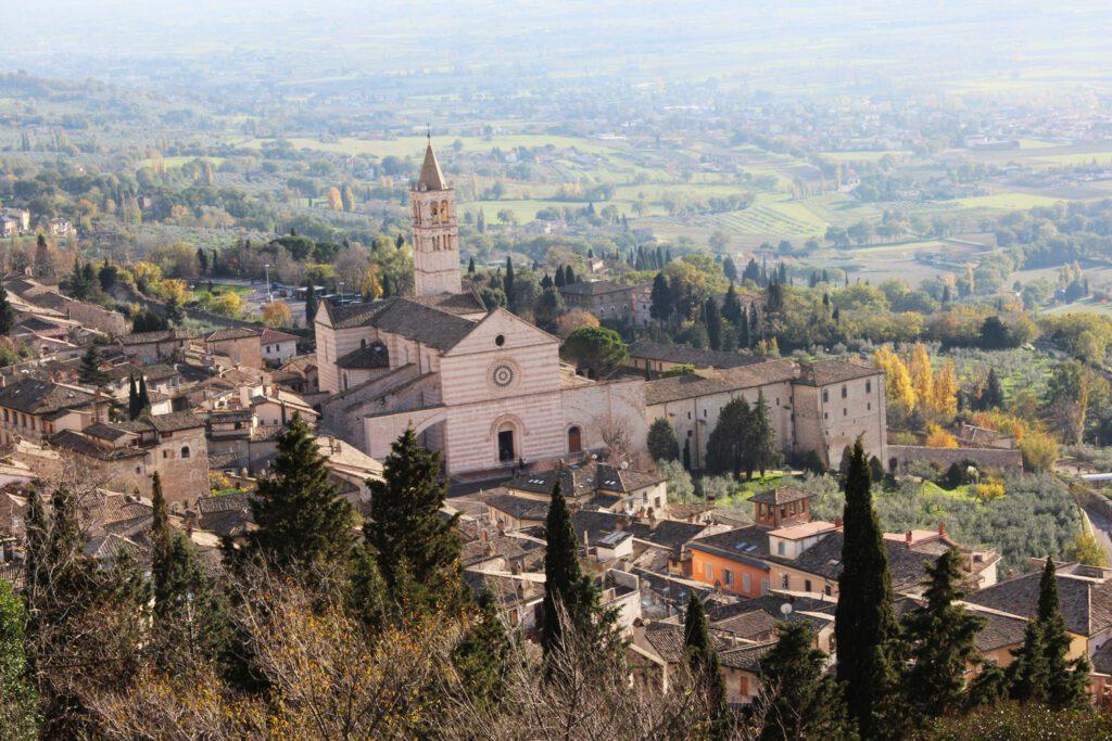 Vista panoramica della Basilica di Santa Chiara ad Assisi. Dall'abitato spuntano l'imponente facciata della chiesa e il suo campanile. Sullo sfondo le campagne umbre.