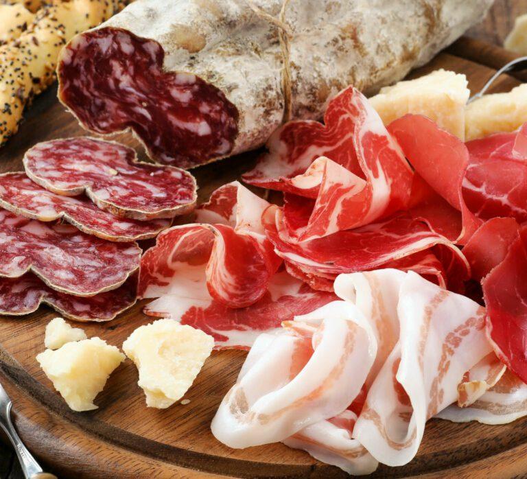 Tagliere di legno con sopra salumi affettati quali: lardo, capocollo, prosciutto e salame. Qualche pezzo di parmigiano e dei grissini sullo sfondo.